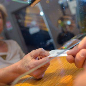 Customer taking ticket from under glass hatch