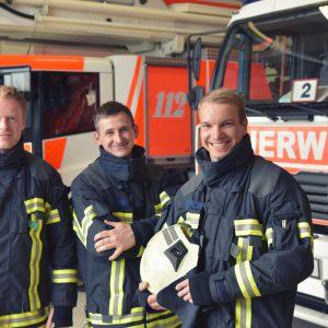 Portrait einer Gruppe Feuerwehrmänner vor den Einsatzfahrzeugen auf der Feuerwache // Portrait of a group of firefighters in front of the fire station vehicles