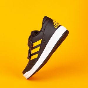 Varna , Bulgaria - AUGUST 13, 2019 : ADIDAS ALTA SPORT  shoe, on yellow background. Product shot. Adidas is a German corporation that designs and manufactures sports shoes, clothing and accessories